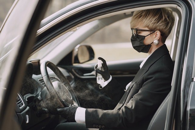 business lady in mask disinfecting car